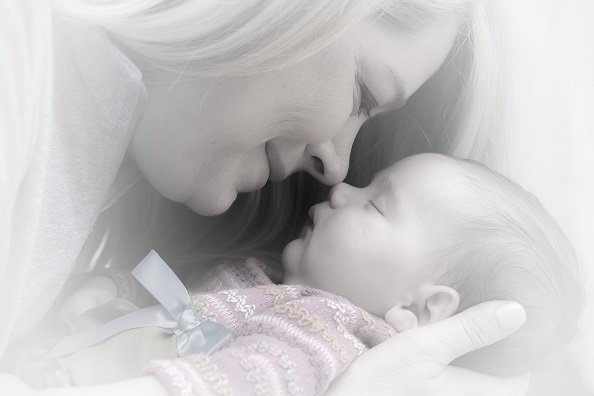 mother kissing baby first month